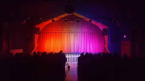 dark theater and stage with lights and curtain closed